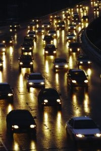 Freeway traffic in the evening, dozens of cars driving in the dark with headlights on