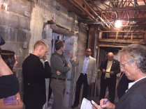 Individuals are taking notes and discussing ideas in a stone building that appears under renovation