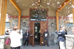 Photo of confetti falling while people watch, taking photos of the doors open to a new business and event center