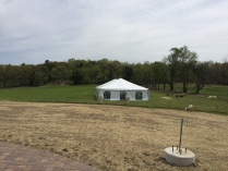 A white tent is set up in a field